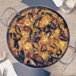 Delicious paella flavored with chorizo, muscles, clams, shrimp and saffron