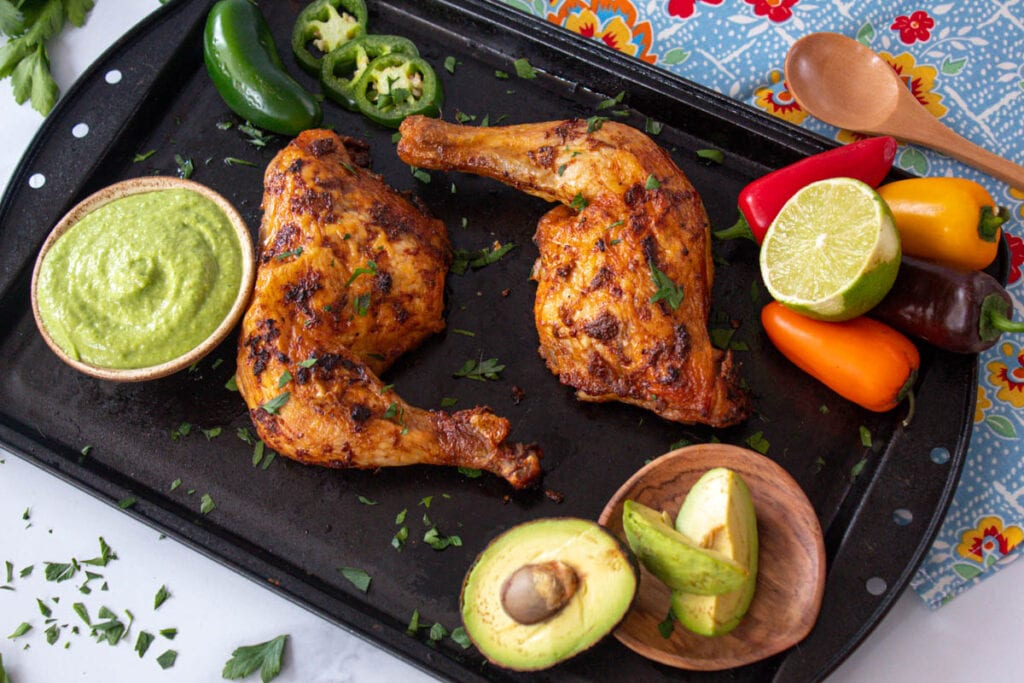 Peruvian chicken on a baking tray with accompaniments