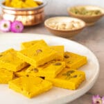 mango barfi squares stacked on a white plate