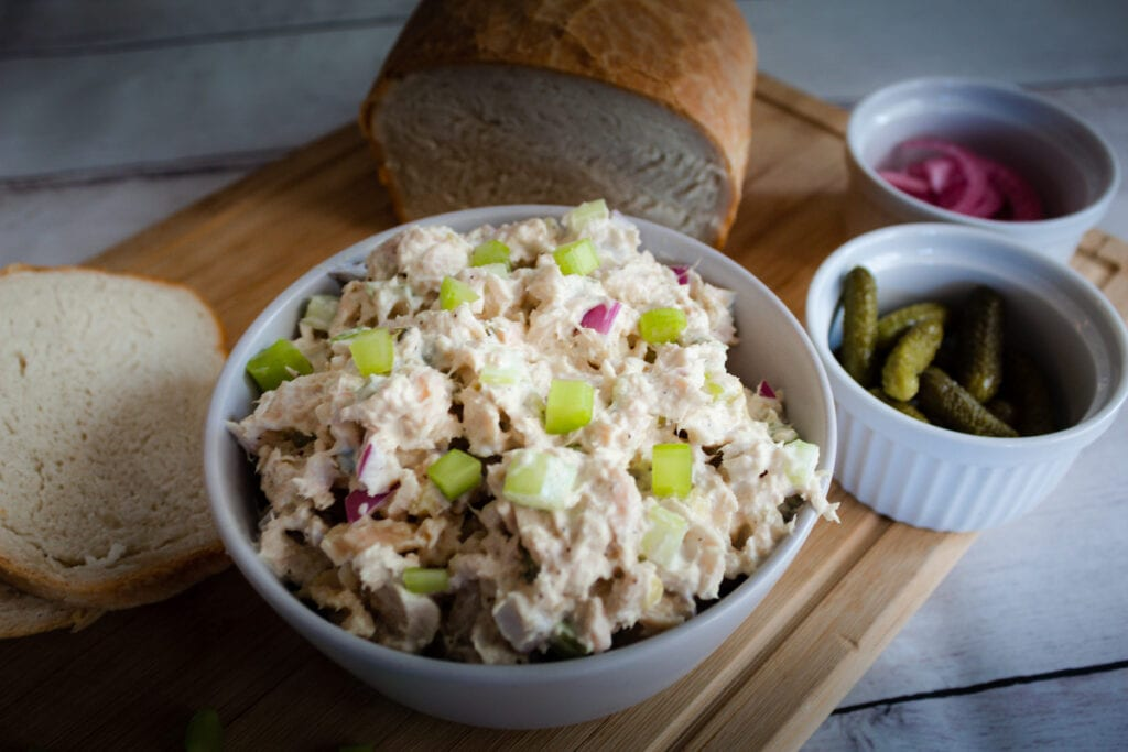 Tuna Salad in a bowl with bread and pickles