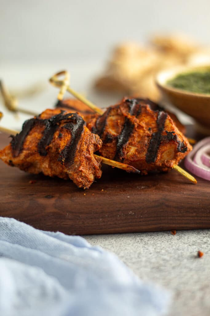 grilled tikka bites on skewers on a wooden plate