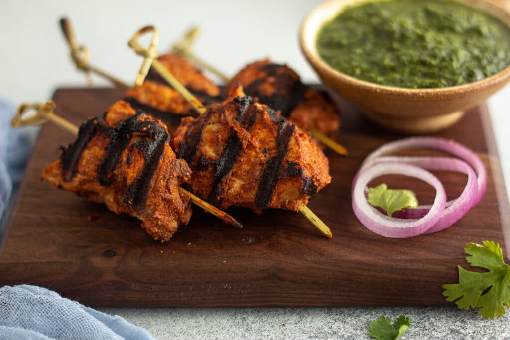head on chicken tikka skewers with pot of chutney in the back