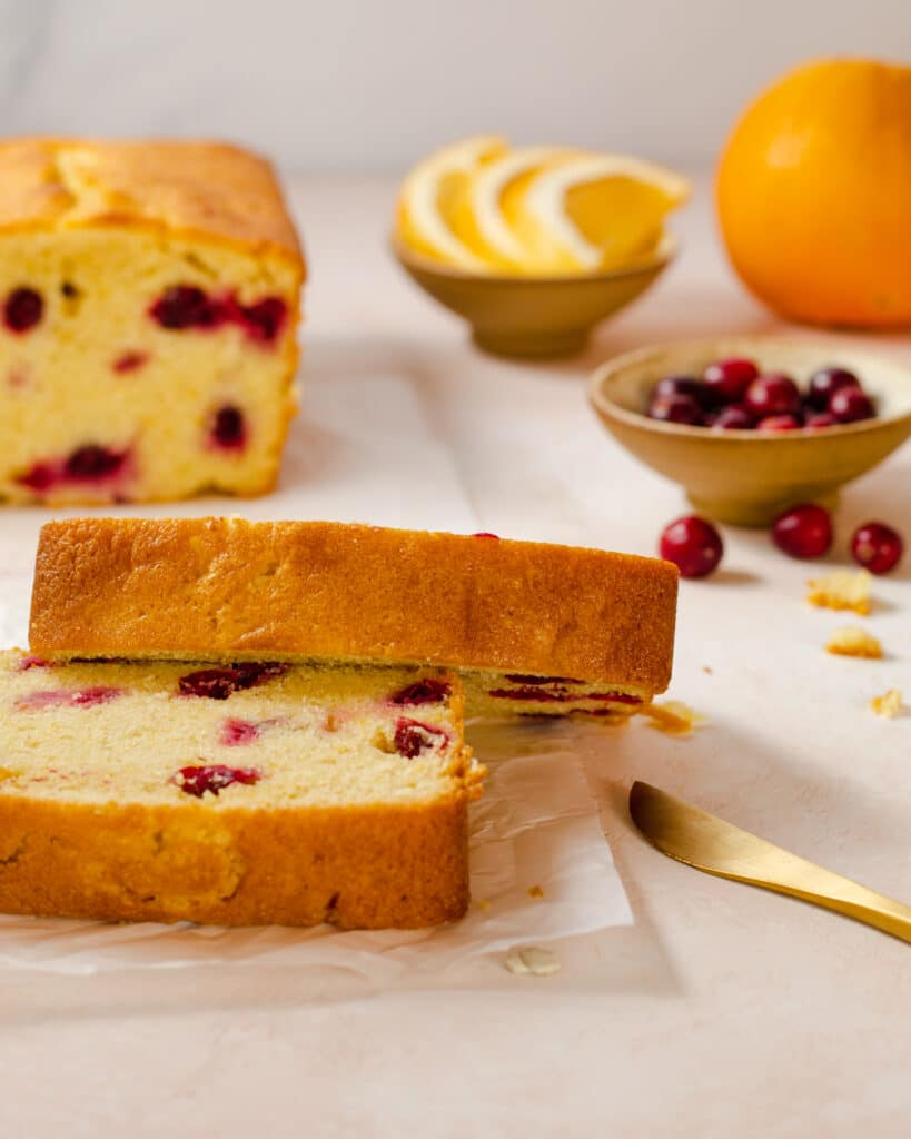 cranberry orange pound cake loaf with slices of cake  in front