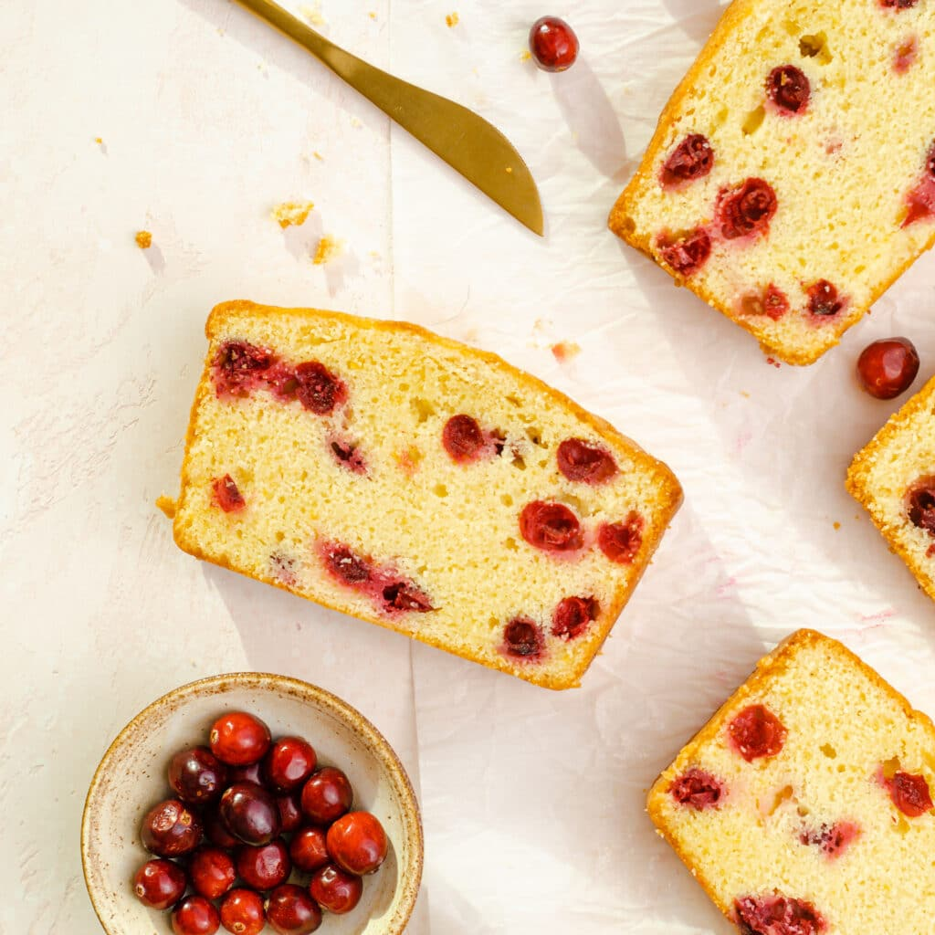 orange and cranberry pound cake slices laid out with a knife and fresh cranberries